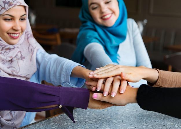 Manos de amigos islámicos apilan para el trabajo en equipo