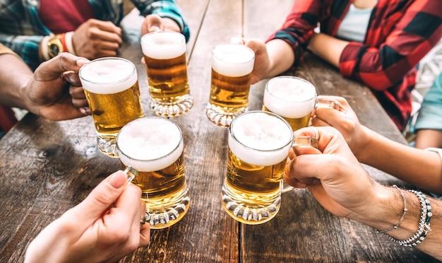 Manos de amigos tostado pintas de cerveza en cervecería pub restaurante