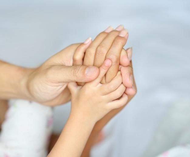 Manos amorosas entrelazadas de padre de familia, madre e hija.