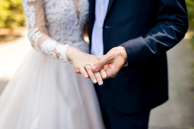 Manos con anillos de boda. novio y novia sesión fotográfica.