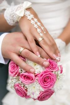 Manos y anillos en bouquet de bodas