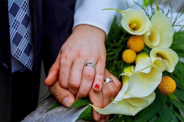 Las manos con los anillos de oro de la boda felices recién casados y ramo de flores kala