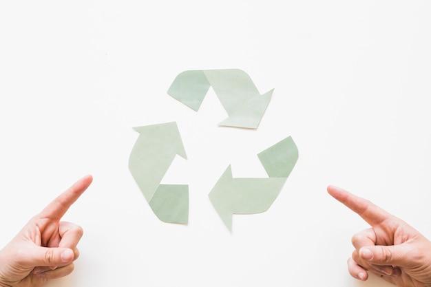 Manos apuntando al logo de reciclaje