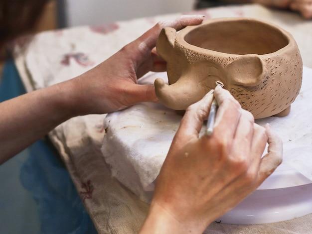 Las manos en arcilla hacen un tazón de cerámica