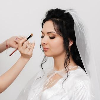 Las manos del artista de maquillaje con un pincel maquilla y aplica sombras en los ojos de la novia de la novia en el salón de belleza