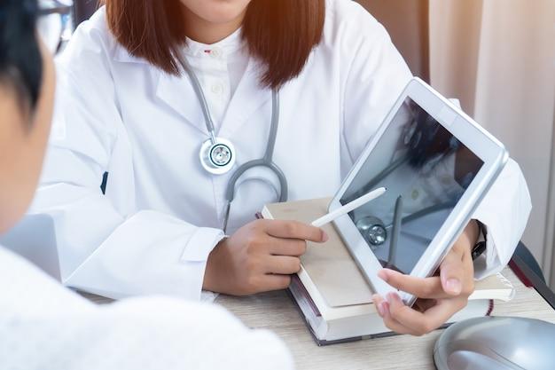 Las manos asiáticas del doctor de la mujer utilizan la aguja que señala el monitor de la tableta para explican al paciente.