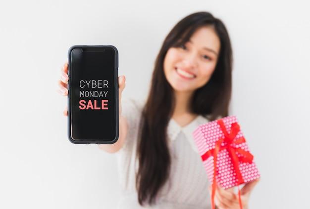 Manos asiáticas hermosas jovenes de la mujer que sostienen la caja de regalo y el smartphone con la pantalla cibernética de lunes