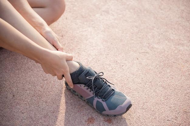 Las manos asiáticas del uso del hombre se sostienen en su tobillo mientras que corre en el camino en el parque.