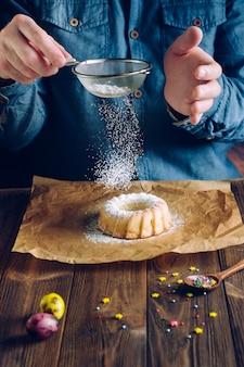 Manos asperjando pastel de pascua con azúcar glas