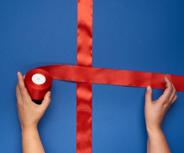 Manos atan una cinta de seda roja en una caja azul