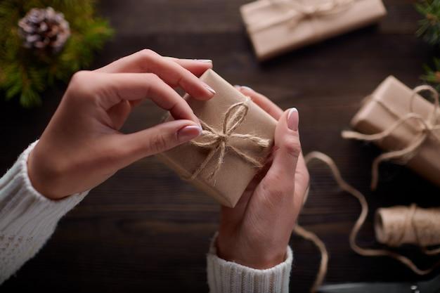 Manos atando el nudo de cordel de paquetes de regalo