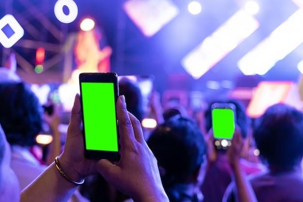 Las manos de la audiencia aprietan a las personas que toman la foto con el teléfono inteligente móvil con pantalla verde en el concierto de la fiesta.