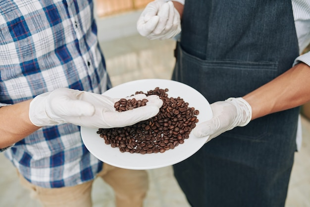 Manos de barista mostrando granos de café tostados de alta calidad al cliente