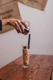 Manos de barista está vertiendo leche haciendo café.
