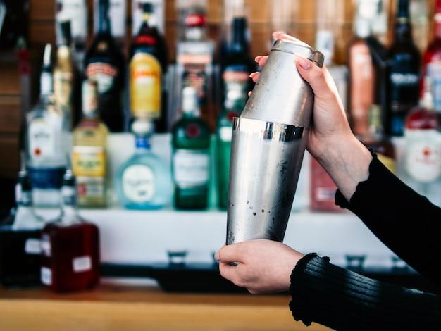 Las manos del barkeeper de la cosecha que preparan la bebida en coctelera