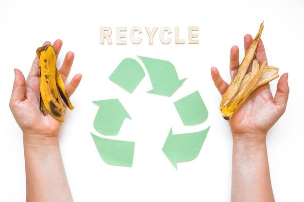 Las manos con basura cerca reciclan la palabra y el logotipo