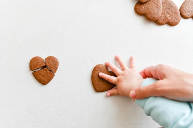 Manos de bebé, corazón frágil, cuidado de la salud, amor y concepto de familia, día mundial del corazón