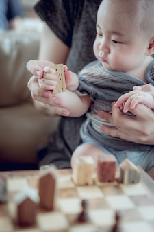 Manos del bebé que sostienen un modelo de la casa con la mano de la madre. el concepto de reubicación, hipoteca, en