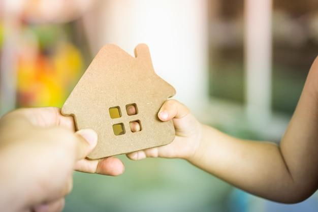 Manos del bebé que sostienen un modelo de la casa con la mano de la madre.