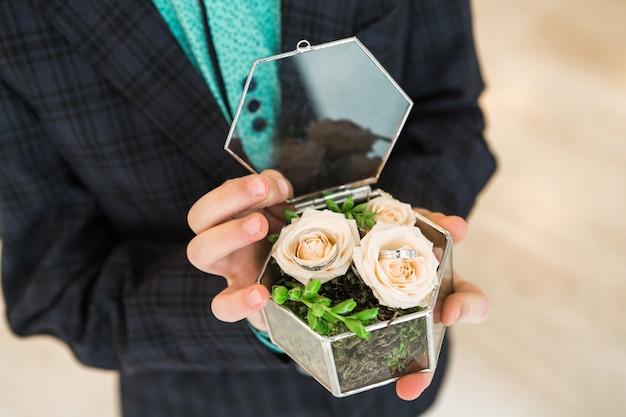 Las manos del bebé sostienen una caja con anillos de boda.