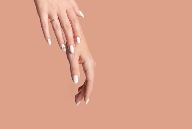Manos de una bella mujer bien arreglada con uñas femeninas sobre un fondo beige.