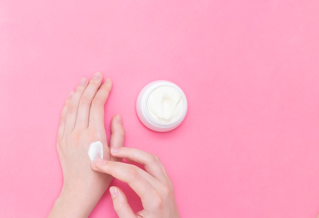 Manos de una bella mujer bien cuidada con un tarro de crema sobre un fondo de textura rosa. crema hidratante para pieles limpias y suaves en invierno. amo el cuerpo concepto de salud.