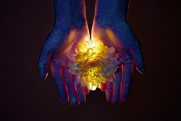 Manos de belleza de una mujer en luz ultravioleta con flores en las palmas. cosméticos para el cuidado de la piel de las manos