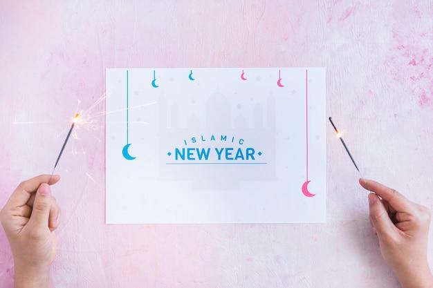 Manos con bengalas y palabras del año nuevo islámico