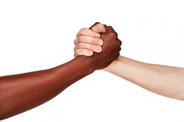 Manos blancas y negras haciendo apretón de manos