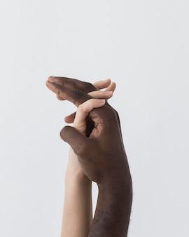 Manos blancas y negras sosteniendo de lado