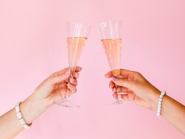 Manos brindando con copas de champaña