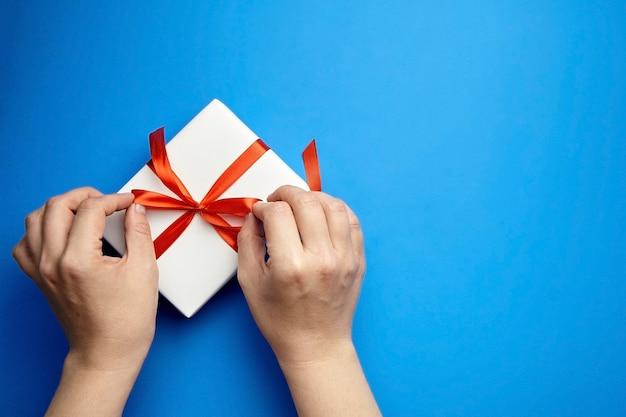 Manos con caja de regalo blanca atada con cinta roja sobre azul