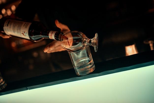 Las manos del camarero, copa de cristal en la barra del bar.