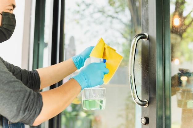 Las manos del camarero con pomo de la puerta desinfectante de alcohol previenen el virus.