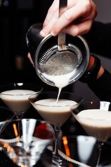 Manos de un camarero sosteniendo una coctelera vertiendo una bebida en una copa de martini.