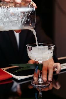 Manos de un camarero sosteniendo una coctelera vertiendo una bebida en un vaso.