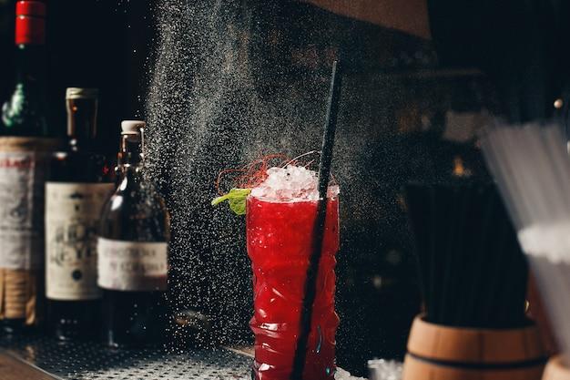 Las manos de los camareros esparcen el jugo en la copa de cóctel con bebida alcohólica.