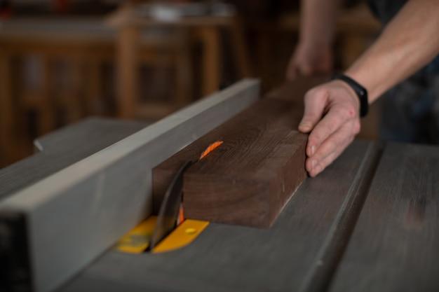 Las manos de carpenter vieron una barra de madera en la máquina con una sierra circular.