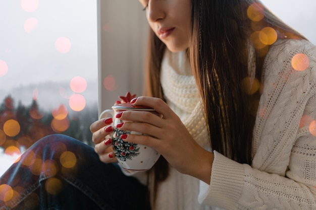 Manos cerca de mujer joven atractiva en elegante suéter de punto blanco sentado en casa en el alféizar de la ventana en navidad sosteniendo la taza bebiendo té caliente, vista de fondo de bosque de invierno, luces bokeh