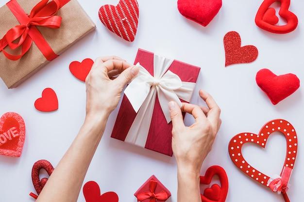 Manos cerca del presente entre conjunto de corazones de adorno.