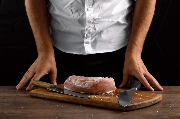 Manos del chef de cerca en la mesa, un trozo de carne, un cuchillo de cocina