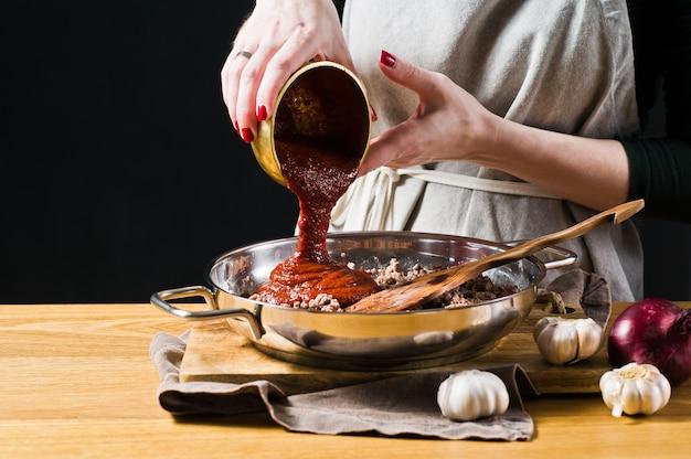 Las manos del chef vierten la pasta de tomate en carne picada