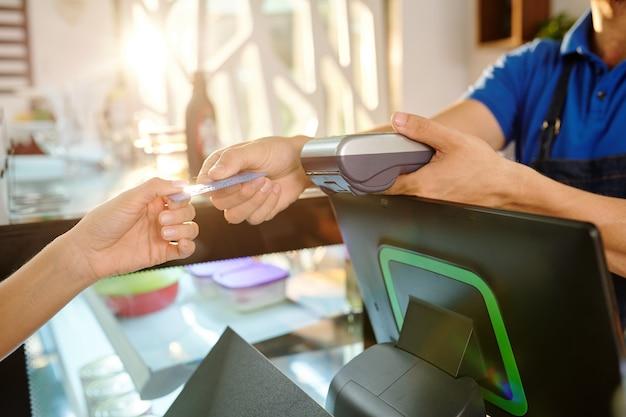 Manos de clienta dando tarjeta de crédito al barista al pagar el café en la cafetería.