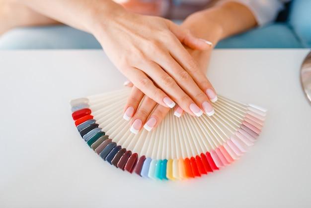 Manos de clienta y paleta de colores de esmalte de uñas en salón de belleza.