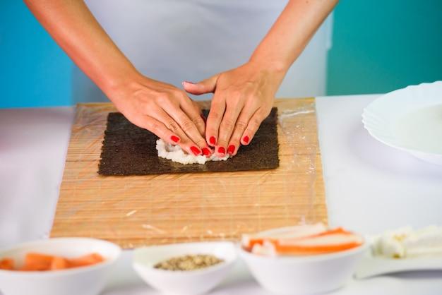 Manos del cocinero de la mujer que llenan rollos de sushi japoneses con arroz en una hoja de la alga marina de nori.