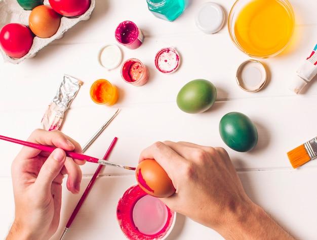 Manos para colorear huevos de pascua cerca del recipiente, pinceles y tinte líquido en un tazón