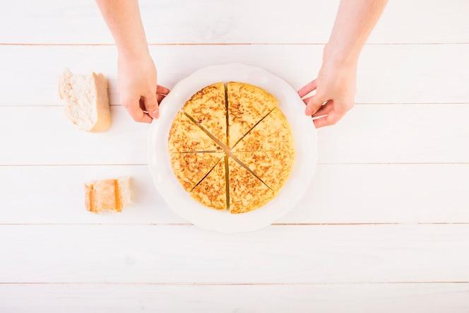 Manos con placa de pastel en la mesa de la cocina