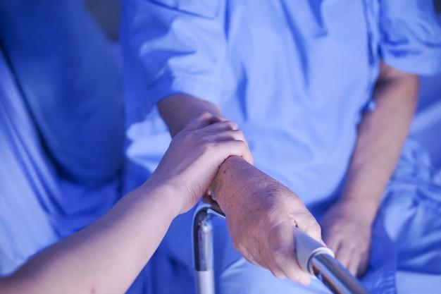 Manos conmovedoras de edad avanzada o anciana anciana mujer paciente con amor y cuidado.