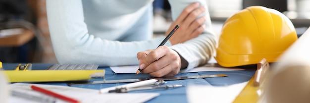 Las manos del constructor del diseñador dibujan el dibujo en la tabla. desarrollo en el campo del concepto de construcción