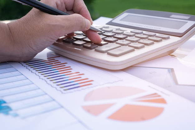 Las manos del contador calculan la tabla de informe financiero gráfico